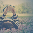Asian woman reading booklet on the grass. Vintage style. — Stock Photo #43947363