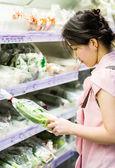 Woman choosing chinese cabbage at supermarket — Stock Photo