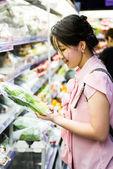 Kvinnan välja kinesisk kål på stormarknad — Stockfoto