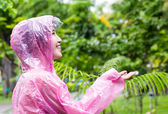 Asian woman in pink raincoat checking for rain in the garden — Stock fotografie
