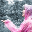 Asian woman in pink raincoat enjoying the rain in the garden — Stock Photo #49369369