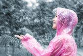 Asian woman in pink raincoat enjoying the rain in the garden — Stockfoto