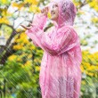 Asian woman in pink raincoat enjoying the rain in the garden — Stock Photo
