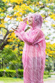Asian woman in pink raincoat enjoying the rain in the garden — Stock fotografie