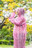 Asian woman in pink raincoat enjoying the rain in the garden — Foto Stock
