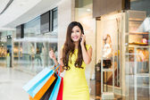 Young woman shopping phoning in mall — Stock Photo