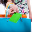 Young woman with shopping bags and credit card on a white backgr — Stock Photo #46680353