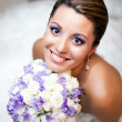 Happy bride holding flowers — Stock Photo