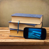 Old books and modern phone — Stock Photo