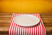 Empty plate on tablecloth — Stock Photo