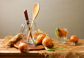 Stillleben mit zwiebeln auf holztisch — Stockfoto