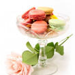 Colorful macaroons and rose on white background — Stock Photo