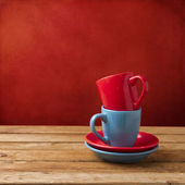 Red and blue coffee cups on wooden table over red grunge wall — Stock Photo