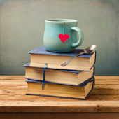 Old vintage books and cup with heart shape on wooden table — Stok fotoğraf