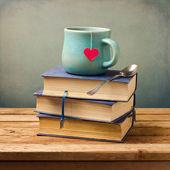 Starych zabytkowych książek i filiżanka o kształcie serca na drewnianym stole — Zdjęcie stockowe