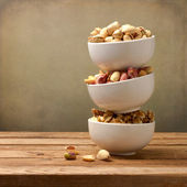 Assorted nuts in dishes on wooden table — Stock Photo