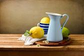 Natürmort ith limon ve ahşap masa üzerinde mavi mine kabı — Stok fotoğraf