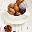 Walnuts and Christmas decor in cup on white tabletop — Stock fotografie