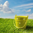 Green bucket on grass over blue sky — Stock Photo #19603483