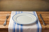 Empty plate with fork and knife on tablecloth — Stock Photo