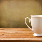 Background with white cup on wooden table over grunge wall — Stock Photo