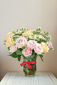 Beautiful rose bouquet over bright wall — Stock Photo