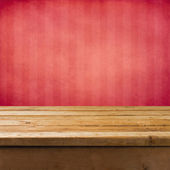 Background with wooden table and pink grunge striped wall — Stock Photo