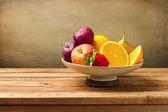 Vaas met vers fruit op houten tafel — Stockfoto