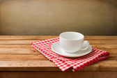 Empty coffee cup on tablecloth on wooden table — Stock Photo