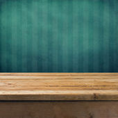 Vintage background with wooden table and grunge blue wall — Stock Photo