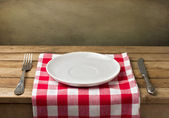 Empty plate on wooden table over grunge background — Stock Photo