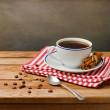 Coffee cup on wooden table over grunge background — Stock Photo