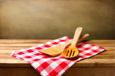 Kitchen utensils on tablecloth on wooden table — Stock Photo