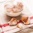 Garlic in white dish on white wooden tabletop — Stock Photo