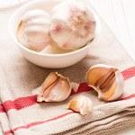 Beyaz ahşap masa üzerinde beyaz tabak sarımsaklı — Stok fotoğraf