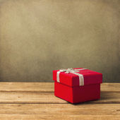 Red small gift box on wooden table — Stock Photo