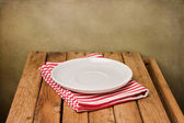 Background with empty plate and wooden table — Stock Photo