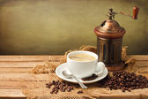 Vintage coffee grinder and coffee cup — Stock Photo