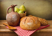 Classical still life with fresh bread and vintage jug — Stock Photo