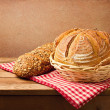 Fresh bread on wooden vintage table over red rough background — Stock Photo