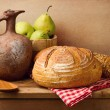 Still life with fresh bread and vintage jug on wooden table — Stock Photo #22667481