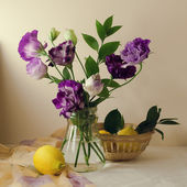 Beautiful purple flowers with lemons — Stock Photo