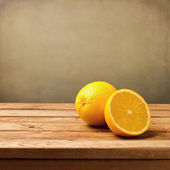 Orange fruit on wooden vintage table over grunge background — Stock Photo