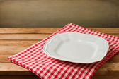 Empty white plate on tablecloth on wooden vintage table — Stock Photo