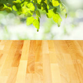 Empty wooden table over leaves bokeh background — Stock Photo