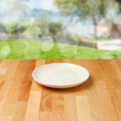 Empty plate on wooden table over nature background — Stock Photo