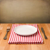 Empty plate with silverware on tablecloth — Stock Photo