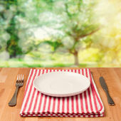Empty plate with silverware on wooden table — Stockfoto