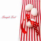 White eggs with polka dots ribbon on red tablecloth — Stock Photo