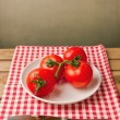 Tomatoes on red tablecloth over grunge background — Stock Photo